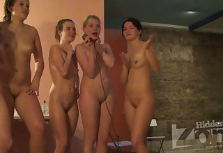 A group of naked girls sings karaoke.