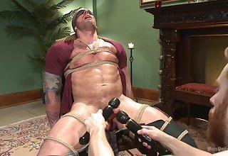 Naked male endures rough bondage with his master